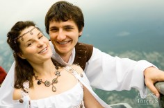 Wedding shot of bride and groom. Couple standing at mountain background. (Man and woman in suits of Middle Ages stile